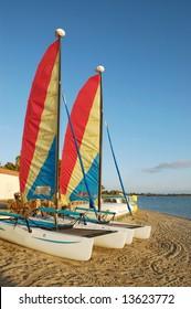 Catamaran sailboats on a beach at sunset; Mission Bay; San Diego, California