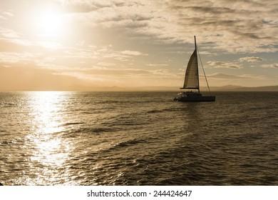 a catamaran sailing in sunset