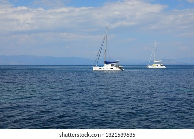 Catamarans in Ionian Sea, Corfu Island, Greece, Europe A catamaran is a multi-hulled watercraft featuring two parallel hulls of equal size. The Ionian Sea is an elongated bay of the Mediterranean Sea.