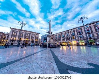 CATANIA, ITALY - CIRCA JUNE 2018: View on historic architecture of the main square as people pass by on the cobblestones streets during dusk circa June 2018 in Catania, Italy.