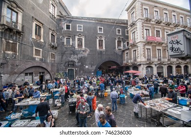 """CATANIA, ITALY - SEPTEMBER 12, 2017: Sellers and buyers on the famous fish market in Catania, Sicily. The market is called """"A´Piscaria"""" and is one of the main city attraction."""