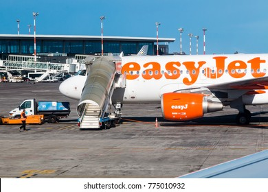 Catania, Sicily- April 2017:An Easyjet airbus A320 aircraft waits on the tarmac at Catania airport.  There is a set of steps at the front door with the airport terminal in the background.