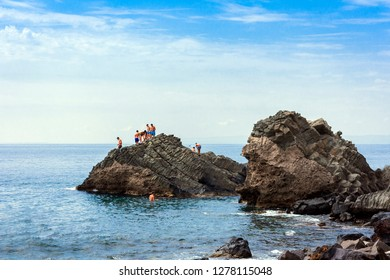 Catania, Sicily, Italy, 08/08/18: children on rocks of the Cyclops in Acitrezza.