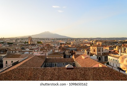 Catania, Sicily in Italy. Aerial view of the city roofs at sunset with the incredible Etna vulcano smoking in the background, nice warm colors and soft light. Shot from the badia of Sant'Agata church