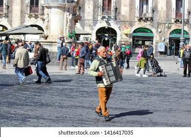 Catania, Sicily, Italy - Apr 10th 2019: Older man busker playing accordion on the Piazza Duomo square in the city center. Cultural street performance.