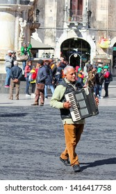Catania, Sicily, Italy - Apr 10th 2019: Older grey man busker playing accordion on the Piazza Duomo square in the old town. Entertaining street performance for gratuity.