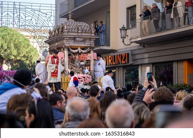 "Catania, Sicily / Italy - February 3 2020: ""Festa di Sant'Agata' t.i. Saint Agatha fest, the priest Padre Narciso Sunda blesses the faithful standing on the holy fercolo next to the statue"