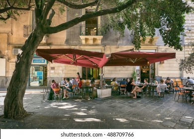 Catania, Sicily, ITALY - JUNE 25 2016 People sitting on the street in the shade under a large tree at the outdoor restaurant