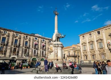 CATANIA, SICILY, ITALY - NOVEMBER 8, 2018: People resting near Elephant Fountain (Fontana dell'Elefante) on Cathedral Square