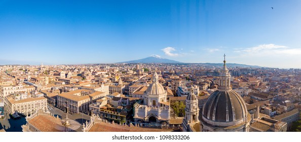Catania, Sicily. May 10, 2018. The dome of Cathedral in Catania on the background of volcano Etna in the snow.. The view of the city of Catania with the view of Etna volcano, Sicily, Italy.