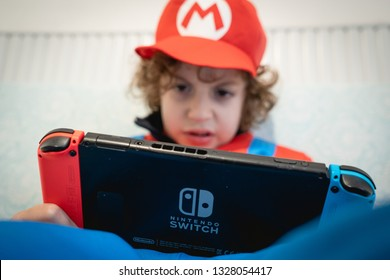 Catania, Sicily/Italy - March 03 2019: Kid cosplaying Super Mario playing on a Nintendo Switch gaming console. Kids addiction to videogame illustrative editorial game.