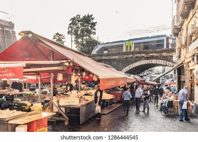 """Catania, Sicily/Italy - Sept 28 2017: A view of the fish market of Catania, with the train walking over the """"archi della marina"""", the typical arches of the city"""