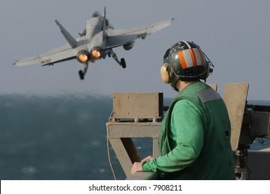 A Catapult Crewman Watches an F/A-18C Hornet Launch From the Nuclear Aircraft Carrier, USS Enterprise