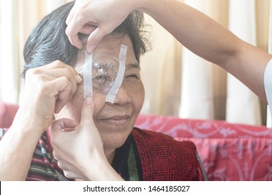 Cataract treatment after surgery by caregiver concept. Asia old woman placed protective shield over her eye taping the cover to protect during naps time.