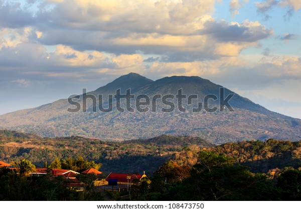 CATARINA, NICARAGUA: View of volcano Mombacho from Catarin mirador. Village buildings in foreground.