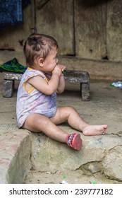 CATCAT, VIETMAN - SEP 20, 2014: Unidentified Hmong little girl eats something in Catcat village, Vietnam. Hmong is a minority ethnic group of Vietnam