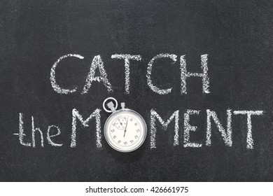 catch moment phrase handwritten on chalkboard with vintage precise stopwatch used instead of O