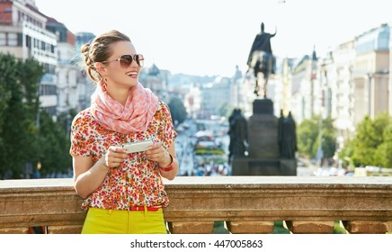 Catch the spirit of old Europe in Prague. Smiling young woman in sunglasses with smartphone standing near National Museum at Wenceslas Square and looking into the distance