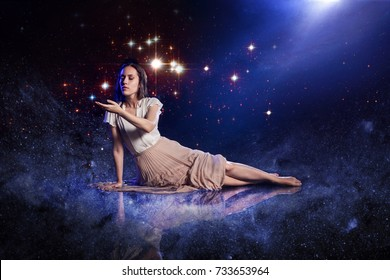 Catch a star, young woman dreams to starry sky. Elements of this image furnished by NASA.