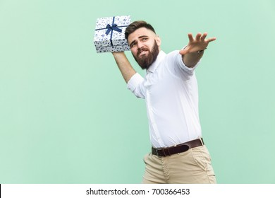 Catch your gift! Young adult man swung and wants to throw off your gift box, isolated on light green background. Studio shot