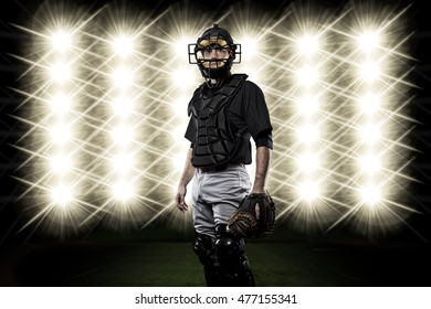 Catcher Player with a black uniform in front of lights.