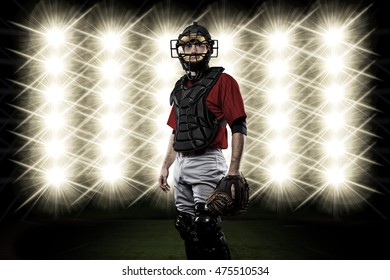 Catcher Player with a red uniform in front of lights.