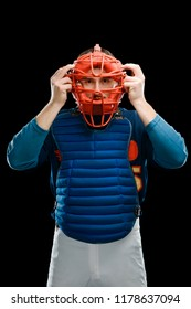 Catcher putting a mask on. Required protection during a baseball game. Half-length portrait on black.