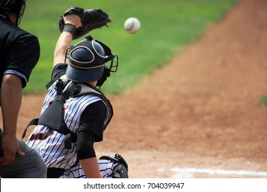 A catcher reaches out to snag it pitch