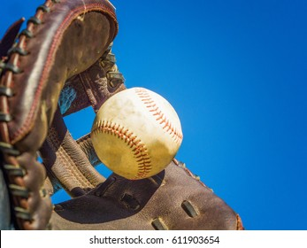 Catching a baseball with a leather glove.