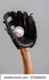 catching baseball with leather baseball glove over gray background