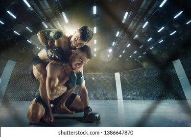 Catching breath. Two professional fighters posing on the sport boxing ring. Couple of fit muscular caucasian athletes or boxers fighting. Sport, competition and human emotions concept.