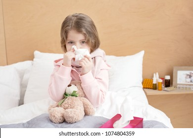 Catching a cold. Poor sick girl lying in bed and blowing her nose