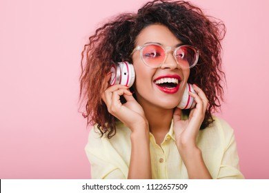 Catching girl with shiny brown skin listening favorite music in big white headphones. Close-up portrait of lovable african female model enjoying her leisure time in studio.