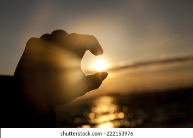 Catching the Sun at sunset time from a man's hand