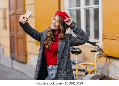 Catching woman with curly hairstyle using smartphone while making selfie near house. Outdoor portrait of laughing french girl in knitted beret taking picture of herself.