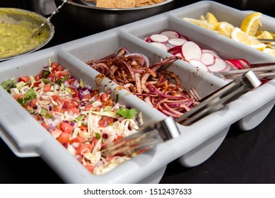 Catered event has traditional Mexican taco makings and delicious flavor additives like onions, cilantro, and pico de gallo.
