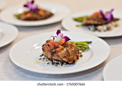 catered food with flowers on white plate