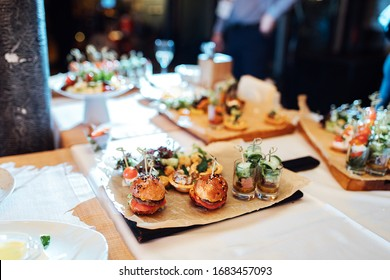 catering area with light snacks for guests, delicious burgers and small portions of salad on tables and trays before a serious business event
