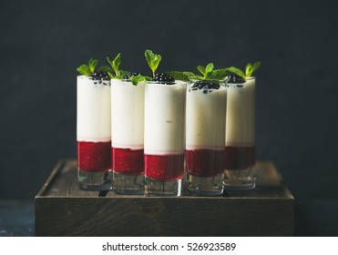 Catering, banquet or party food concept. Dessert in glass with blackberries and mint leaves over dark background on corporate event, christmas, birthday, wedding celebration, selective focus