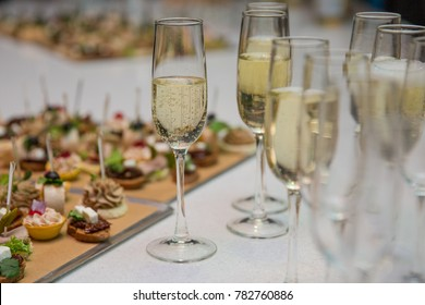 Catering Banquet table with canapes, snacks, festive table, slices, glasses