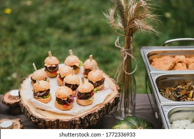 Catering banquet table at reception. Casual wedding party. Food styling, appetizers bar, welcome drink, event design.