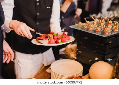 Catering banquet table at reception. Restaurant presentation, molecular gastronomy, haute cuisine, food consumption, party concept. Waiter serving strawberry.