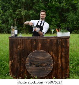 Catering bar service, bartender workplace. Handsome caucasian barman adding some ice cubes in a glass. Concept of small business and preparation cocktail
