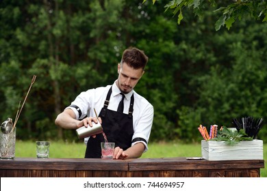 Catering bar service, bartender workplace. Handsome caucasian barman adding some liquid in a glass. Concept of small business and preparation cocktail