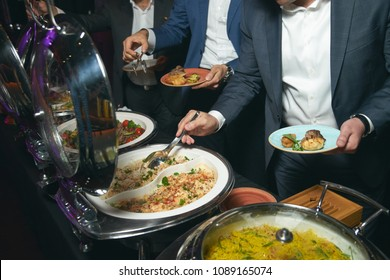 Catering buffet food indoor in luxury restaurant with meat colorful fruits and vegetables. People at a banquet taking different food. Colleagues Buffet Party Brunch Dinning Concept