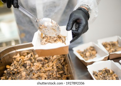 Catering, a cook in the kitchen in a white robe and gloves prepares food in disposable containers