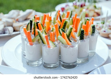 Catering for party. Close up of appetizers with carrots, cucumber sticks, cream cheese and spices in short glasses on white table.