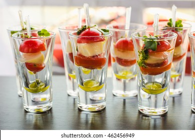 Catering for party. Close up of appetizers with cherry tomatoes, green olives, olive oil, cheese and spices in short glasses on wood brown table.