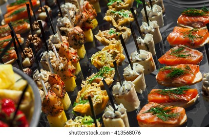 Catering service . appetizing sandwiches on plastic sticks range meat, fish, vegetable canapes on a festive wedding table outdoor.