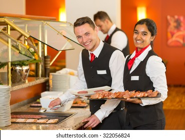 Catering service employees filling buffet at a restaurant or hotel